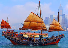 The chinese junk boat at victoria harbor, hong kong. Tourists enjoying the chinese junk ride at victoria harbor in hong kong Royalty Free Stock Image