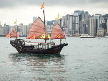 Chinese Junk In Hong Kong Harbor. HONG KONG - MAY 17, 2013: A traditional Chinese junk sails the waters of Victoria Bay taking tourists on a tour of the main Royalty Free Stock Image
