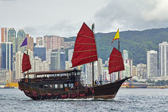 Chinese Junk in Hong Kong Harbor. A chinese junk sails across Victoria Harbor, Hong Kong Royalty Free Stock Images