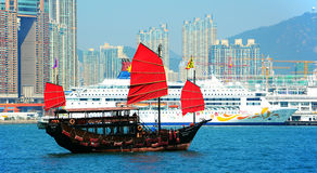 Chinese junk in hong kong. Traditional chinese junk and a luxury cruise at victoria harbor in hong kong Royalty Free Stock Images