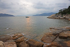 Chinese junk in Hong Kong waters with a rocky foreshore in the late afternoon. From Cheung Chau island Hong Kong Stock Images
