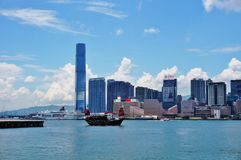 A Chinese junk ship in front of the Hong Kong skyline. HONG KONG - A Chinese junk ship passes in the Hong Kong harbor in front of the modern Kowloon skyline Royalty Free Stock Images
