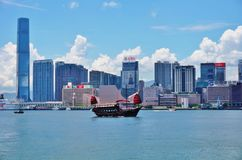 A Chinese junk ship in front of the Hong Kong skyline. HONG KONG - A Chinese junk ship passes in the Hong Kong harbor in front of the modern Kowloon skyline Royalty Free Stock Photos