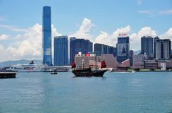 A Chinese junk ship in front of the Hong Kong skyline. HONG KONG - A Chinese junk ship passes in the Hong Kong harbor in front of the modern Kowloon skyline Royalty Free Stock Image