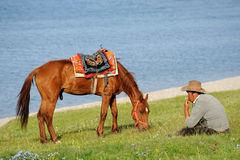 Chinese Kazakh herdsmen  with horse at Sailimu lak Royalty Free Stock Images