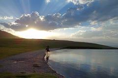 Chinese Kazakh herdsmen ride horse. In Sailimu lake,xinjiang,China Royalty Free Stock Photography