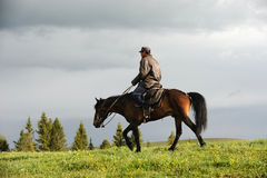 Chinese Kazakh herdsmen  riding  horse in grasslan Royalty Free Stock Image