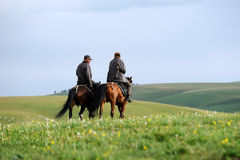Chinese Kazakh herdsmen riding horse in grassland Royalty Free Stock Photo