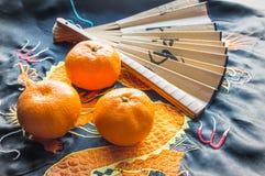 Chinese Kerstmis decoratie-traditionele document ventilator en mandarijnen op zijdestof, achtergrond met geborduurde draak stock foto's