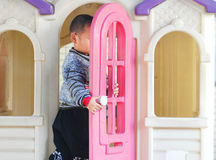 A chinese kid and a doll house Royalty Free Stock Photos