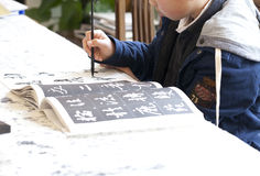 Chinese kid practice calligrapy. On paper Stock Image