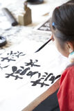 Chinese kid practice calligrapy. On paper Royalty Free Stock Photo