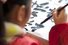 Chinese kid practice calligrapy. On paper Stock Photography