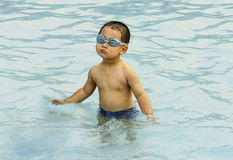 Chinese kid swimming. A candid picture of a chinese boy playing water in a swimming pool Royalty Free Stock Image