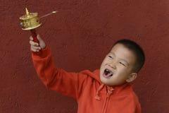 Kid turning prayer wheel. Chinese kid turning prayer wheel with red wall background Stock Photo