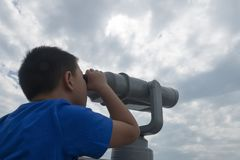 Chinese kid using telescope lookout stock photography