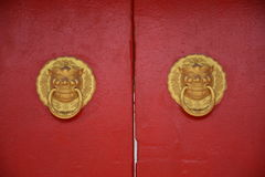 Chinese knocker. Asian doors opening with its protective gargoyles which also serve as knockers and handles Royalty Free Stock Photo