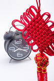 Chinese knot and alarm clock  on white Royalty Free Stock Photography