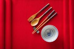 Chinese kom, vork, lepel en eetstokjes op rode mat royalty-vrije stock fotografie
