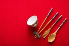 Chinese kom, vork, lepel en eetstokjes op rode mat stock foto's
