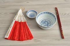 Chinese kommen, eetstokjes en een handventilator stock fotografie