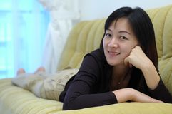 Chinese lady. A young chinese asian lady looking at the camera,relaxing at home sofa Stock Photos