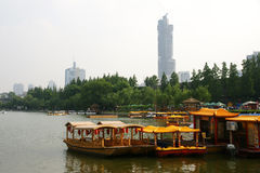 Chinese lake with boats. A lake in China with traditional boats and skyscrapers in the distance Royalty Free Stock Photos