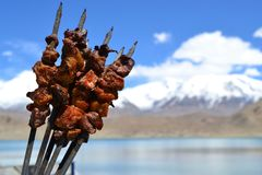 Chinese lamb meat skewers in Xinjiang Uyghur style barbeque, in mountains Karakul lake royalty free stock image
