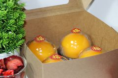 Chinese language : bliss, stick on four orange cakes in the box and out focus green leaf with on white floor stock images