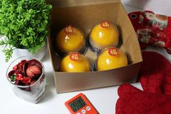 Chinese language : bliss, stick on four orange cakes in the box with red kitchen glove and red fabric bag and green leaf and stock photo
