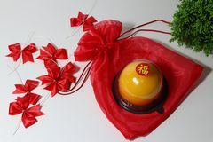 Chinese language : bliss, stick on the orange cake on the red fabric bag and red ribbon and green leaf on white floor royalty free stock images