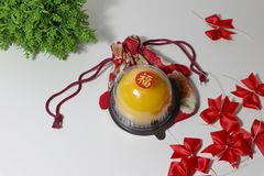 Chinese language : bliss, stick on the orange cake on the red fabric bag and red ribbon and green leaf on white floor. Chinese New Year concept stock images
