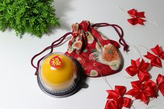 Chinese language : bliss, stick on the orange cake on the red fabric bag and red ribbon and green leaf on white floor. Chinese New Year concept royalty free stock photo