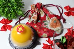 Chinese language : bliss, stick on the orange cake on the red fabric bag and red ribbon and green leaf on white floor. Chinese New Year concept royalty free stock image
