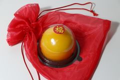 Chinese language : bliss, stick on the orange cake on the red fabric bag on white floor. Chinese New Year concept royalty free stock photos