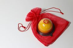 Chinese language : bliss, stick on the orange cake on the red fabric bag on white floor. Chinese New Year concept royalty free stock image