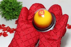 Chinese language : bliss, stick on the orange cake in the red kitchen glove and out focus red ribbon and green leaf on white floor. Chinese New Year concept royalty free stock photography