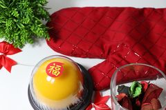 Chinese language : bliss, stick on the orange cake in the red kitchen glove and red ribbon and dried flower and green leaf on royalty free stock images