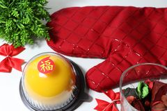 Chinese language : bliss, stick on the orange cake with red kitchen glove and red ribbon and green leaf on white floor stock photos