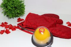 Chinese language : bliss, stick on the orange cake with red kitchen glove and red ribbon and green leaf on white floor. Chinese New Year concept royalty free stock photo