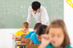 Chinese language classroom. Male Chinese language teacher in classroom with group of elementary students stock image
