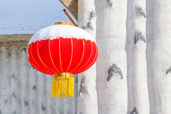 Chinese lantern attached to white house. Chinese lantern attached to white wooden house with snow Stock Image