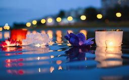 Chinese lanterns floating in river at night with city lights Royalty Free Stock Photos