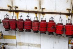 Chinese lanterns. Small lanterns (red) hanging on a rail in the back a white wooden wall Stock Photos