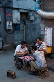 Chinese lifestyle. Some chinese people play a traditional game in a hutong in Beijing Royalty Free Stock Images