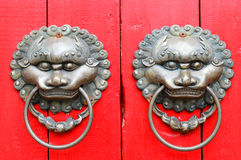 Chinese lion door knockers. Pair of traditional Chinese metal door knockers on red wood in shape of lions Stock Images