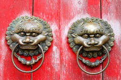 Chinese lion door knockers. Closeup of two metal Chinese door knockers on red wooden door Stock Photo