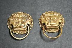 Chinese lion door knockers. A pair of traditional chinese gold lion head door knockers royalty free stock photo
