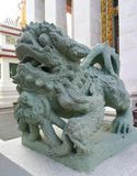 Chinese Lion green granite statue, Thai religion Chinese fetish. Lion statue, garden and big jar in background with sun ray Royalty Free Stock Photo