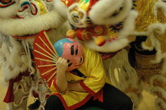 Chinese Lions and Man. Two Chinese Lions dancing and trying to wake the man in the mask. Seen as part of Chinese New Year celebrations and ceremony Stock Images